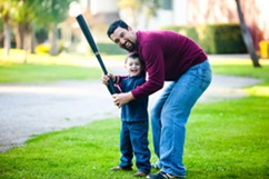 Dad and son learning how to hold a bat
