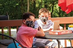 Two boys wearing masks playing on their electronic devices