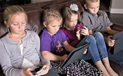 Children sitting on couch using various types of electronics or screens.