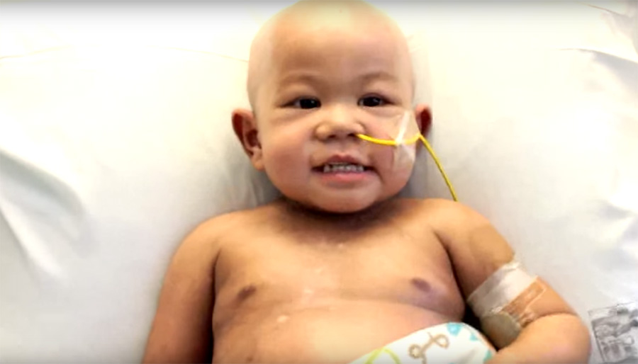 Toddler boy in hospital bed with tubes in nose